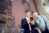 Business colleagues using mobile phone outside office building at night