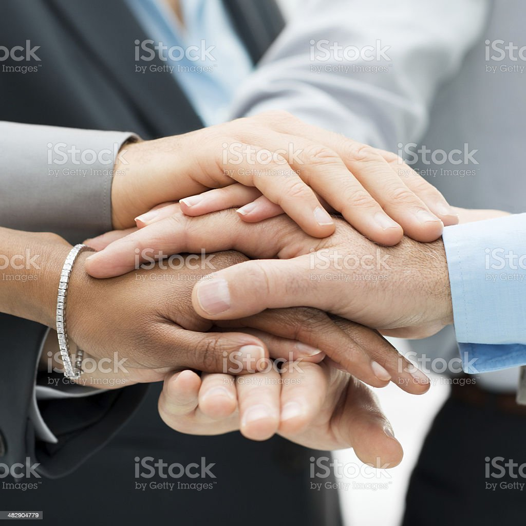 Business colleagues with hands stacked together stock photo