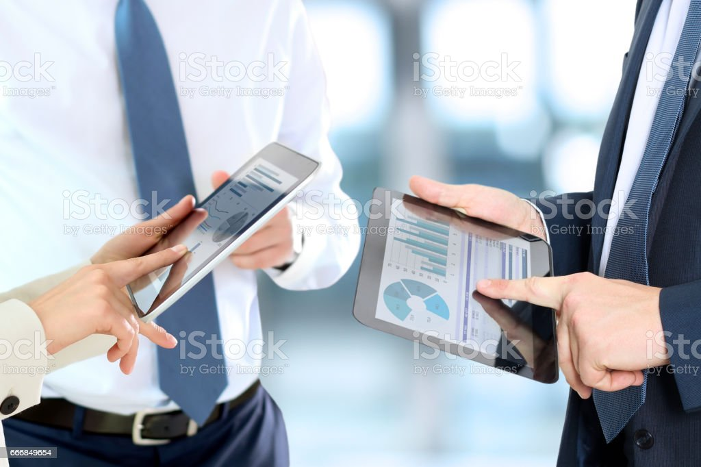 Business colleagues working and analyzing financial figures on a digital tablet stock photo
