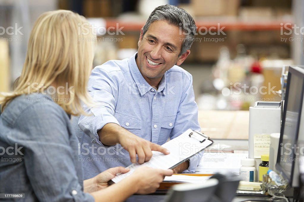 Business Colleagues Working At Desk In Warehouse stock photo