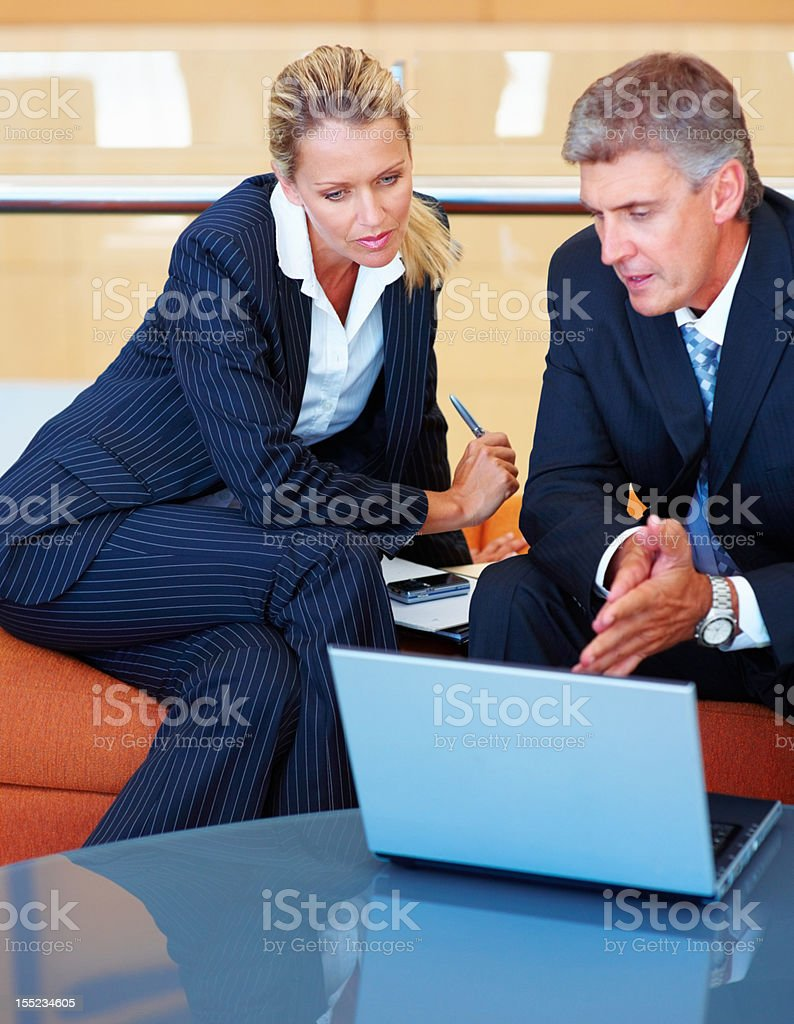 Business colleagues working on a laptop royalty-free stock photo