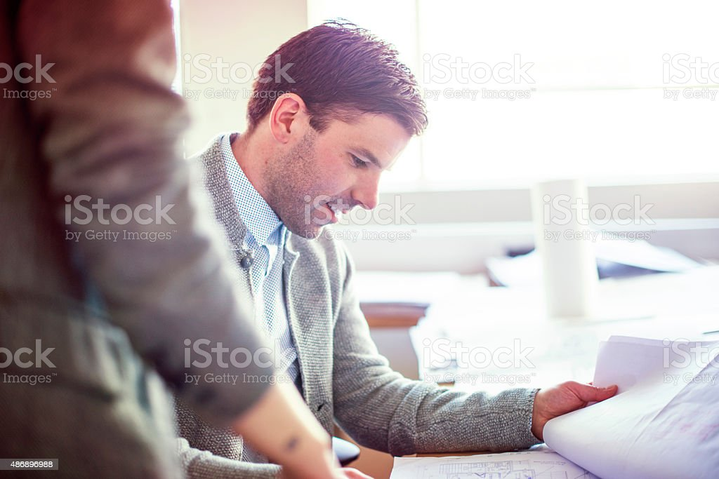 Business colleagues working on blueprint in office stock photo