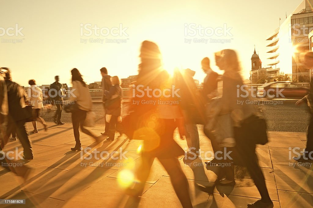 Business Commuters Walking Home After Work, Sunset Backlit, Blurred Motion stock photo