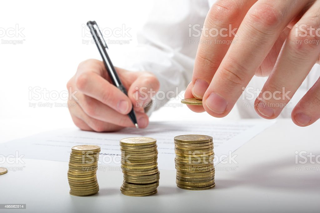 Business concept. Businessman's hand counting money on calculator stock photo