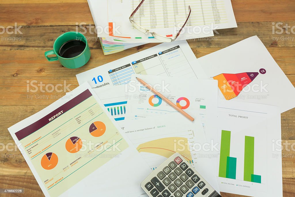 Business concept of a pencil, charts, eyeglasses, calculator, coffee cup stock photo