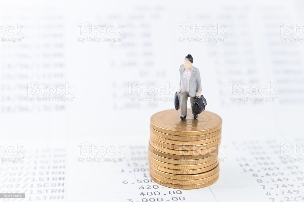 Business concept with miniature people workers on money coin piles. stock photo