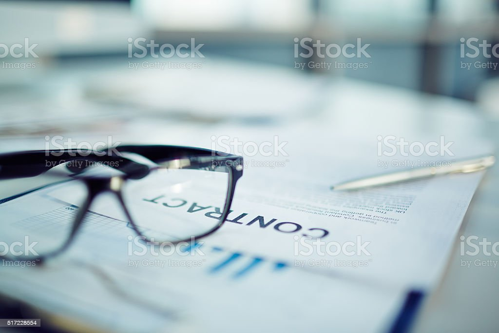 Close-up of business documents with glasses on the table
