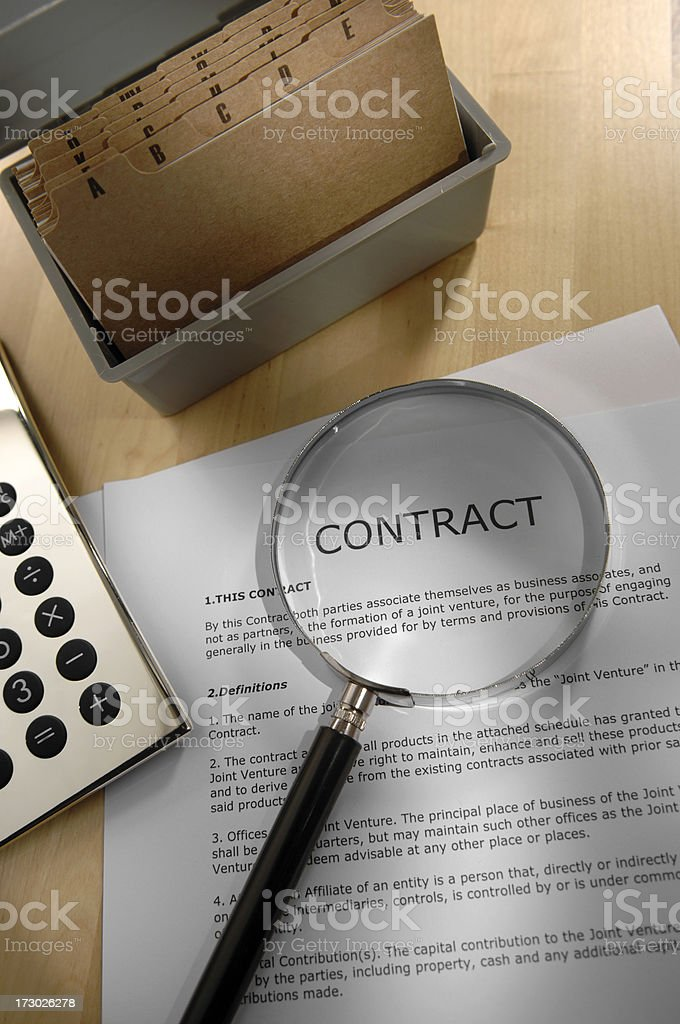 Business contract with magnifying glass to read small print. royalty-free stock photo