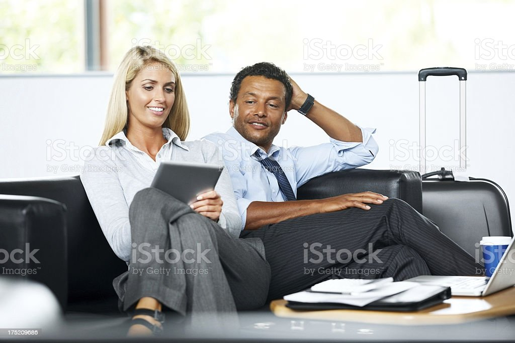 Business couple at airport lounge using tablet PC royalty-free stock photo