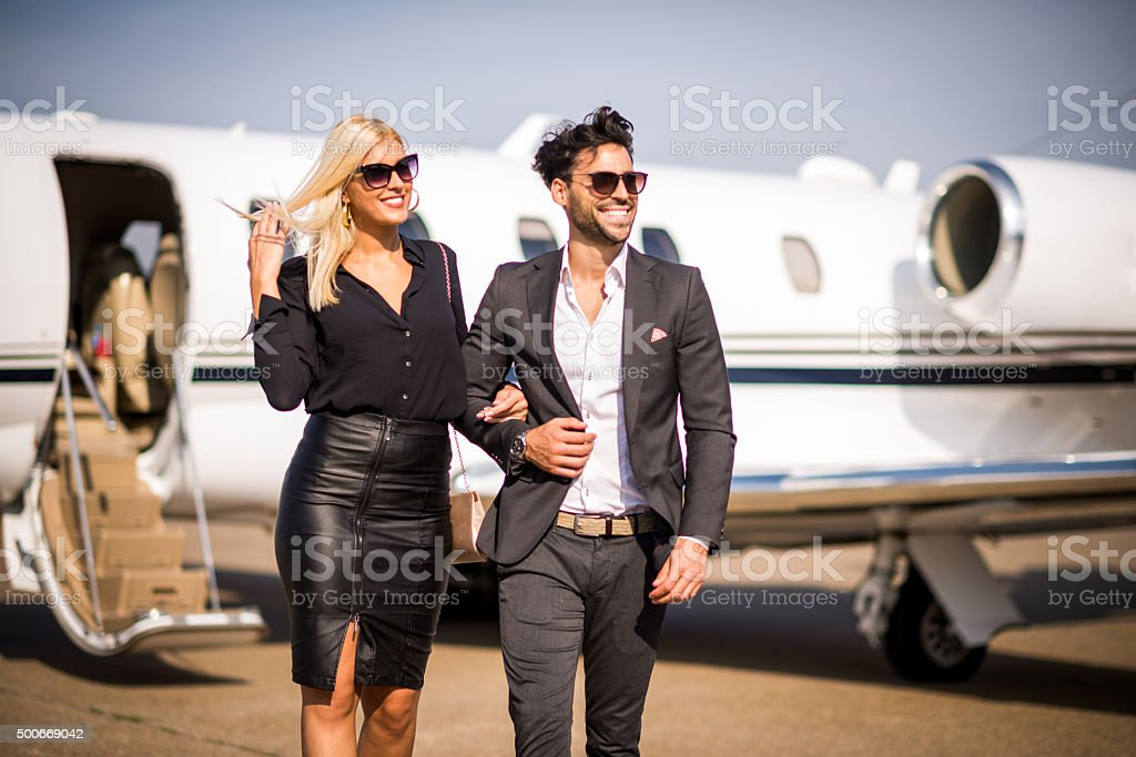 Business couple leaving private airplane stock photo