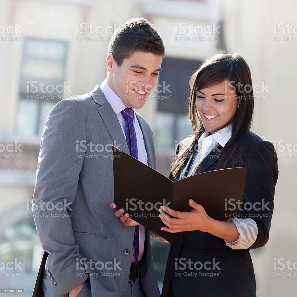 Business couple outdoors with files. royalty-free stock photo