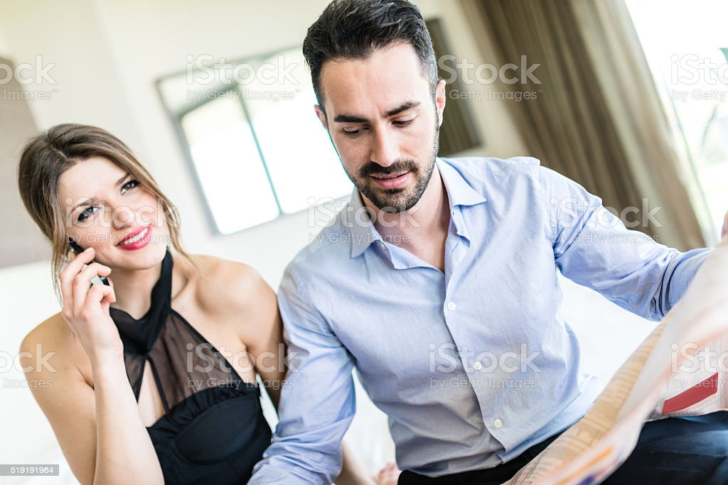 business couple reading newspaper on bedroom stock photo
