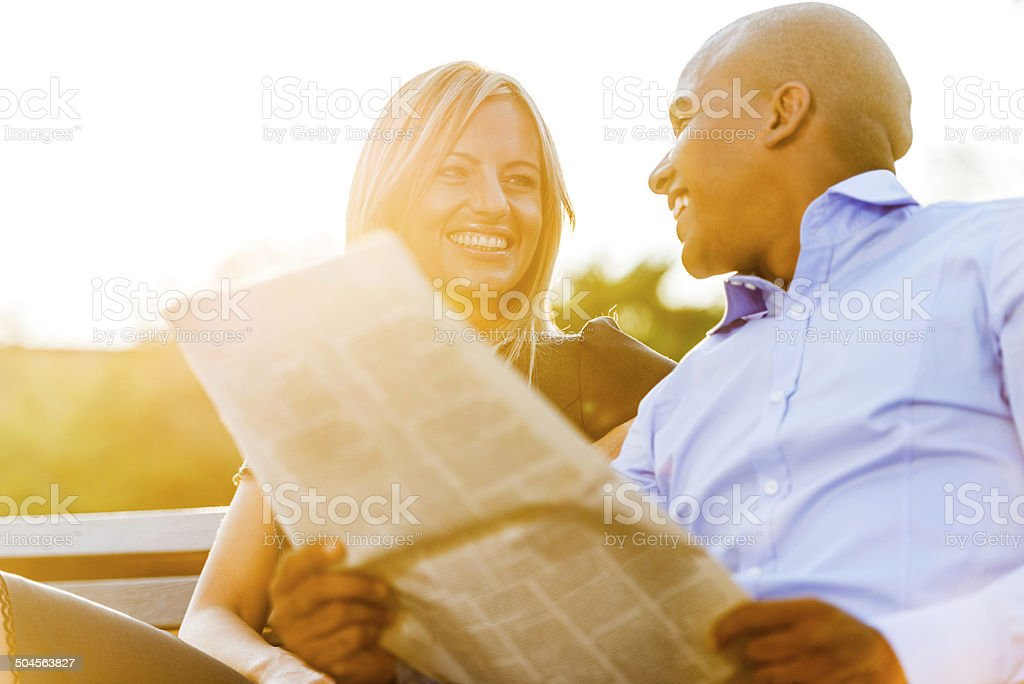 Business couple reading newspapers at sunset. stock photo