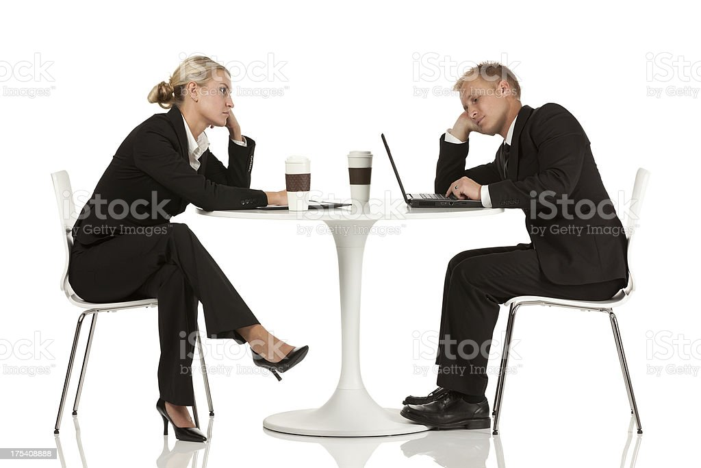 Business couple sitting in a restaurant looking sad royalty-free stock photo