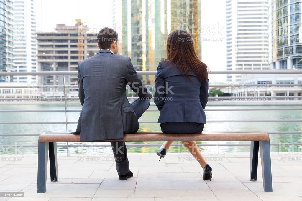 Business couple sitting on bench stock photo