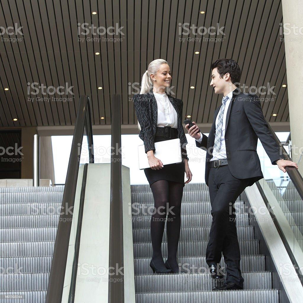 Affaires couple parlant sur un escalier roulant. photo libre de droits