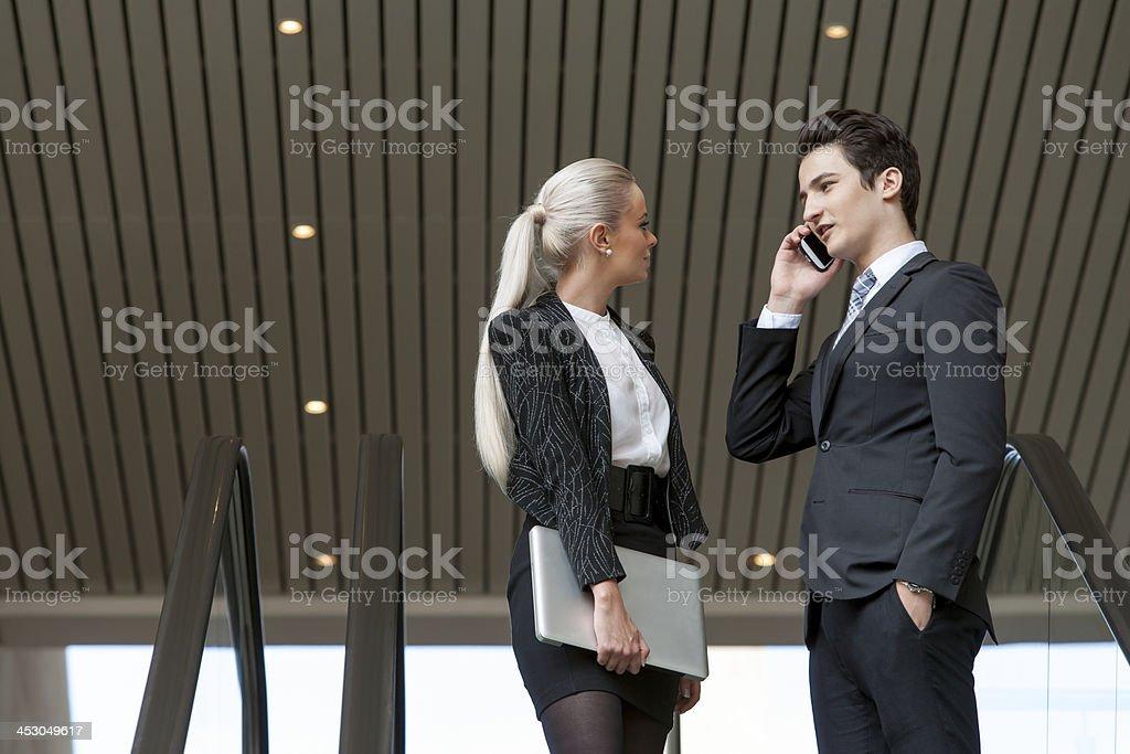 couple d'affaires, parler au téléphone dans le centre commercial. photo libre de droits