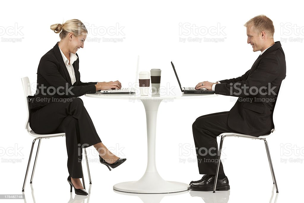 Business couple using laptop in a restaurant royalty-free stock photo