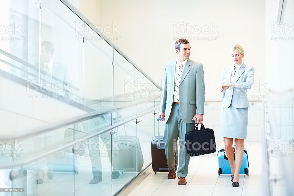 Business couple with travel bags while woman checking out time stock photo