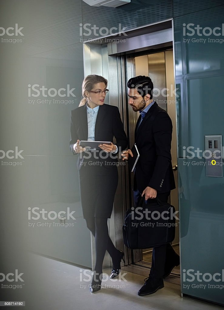 Business coworkers  walking out of elevator stock photo