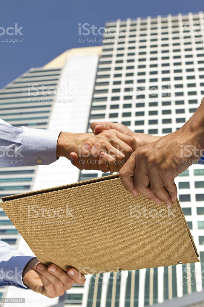Business deal with a file report in a financial district royalty-free stock photo