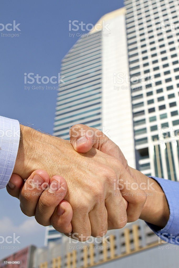 Business deal with a handshake in a financial district royalty-free stock photo