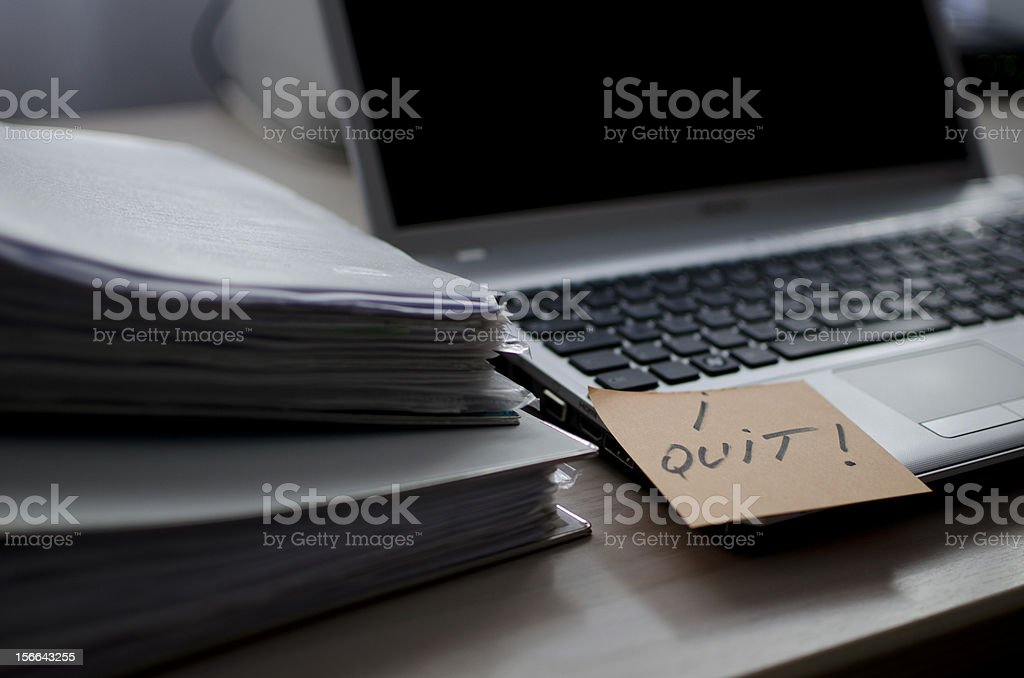 A business desk and laptop with an I quit post it  stock photo