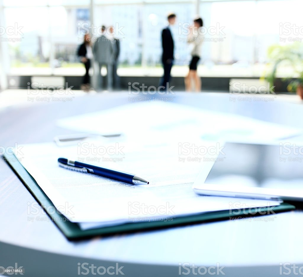 business document lying on the desk, office workers interacting stock photo