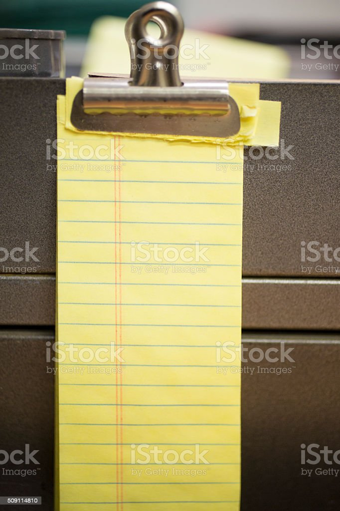 Business, education. Blank yellow notepad on metal filing cabinet. stock photo