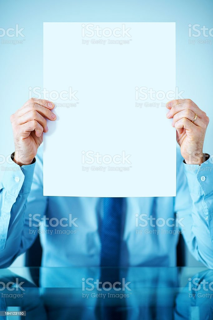 Business executive holds blank board in front of his face royalty-free stock photo
