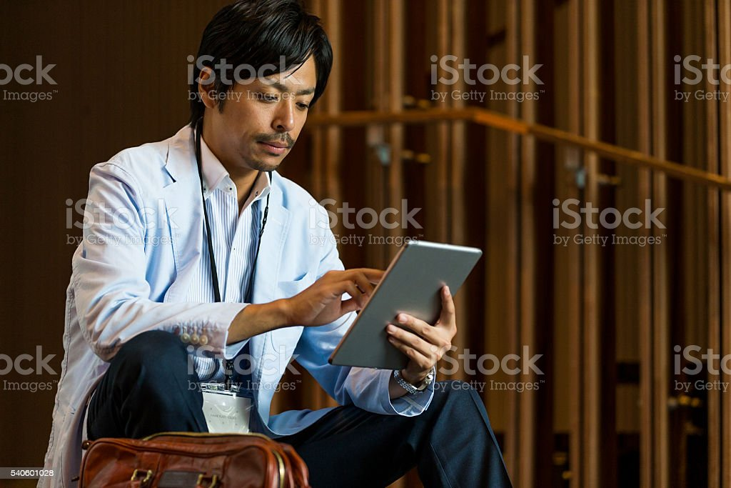 Business Executive reading email on his digital tablet stock photo