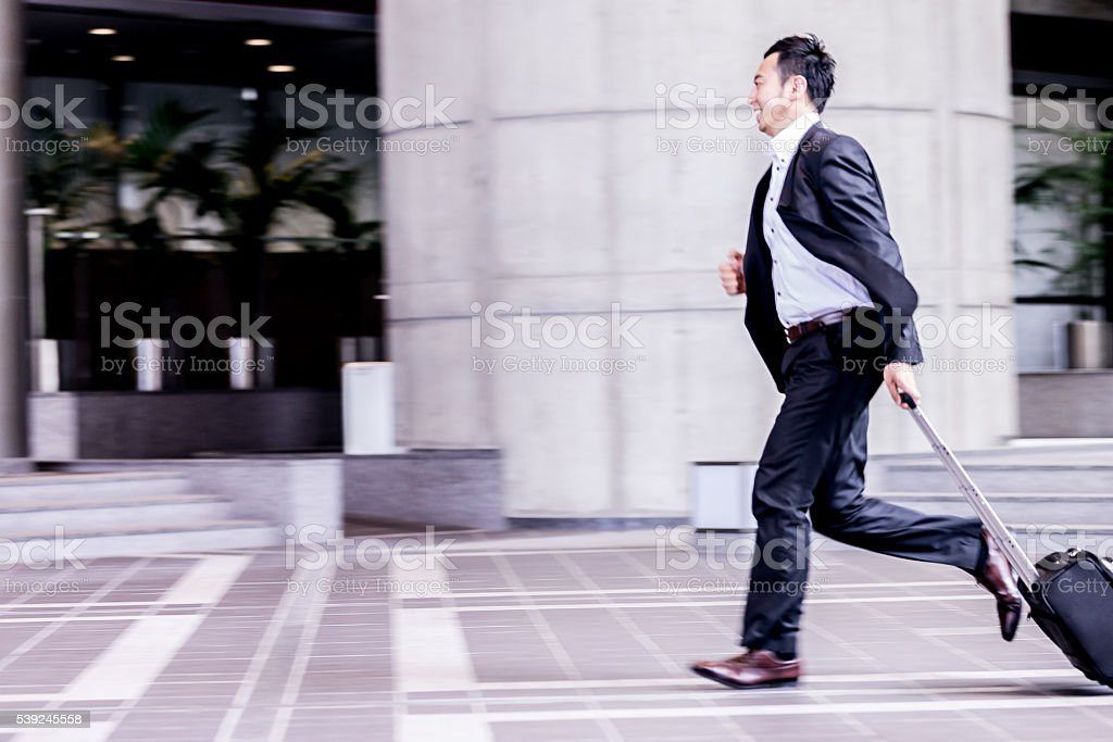 Business executive running to catch his next meeting. stock photo