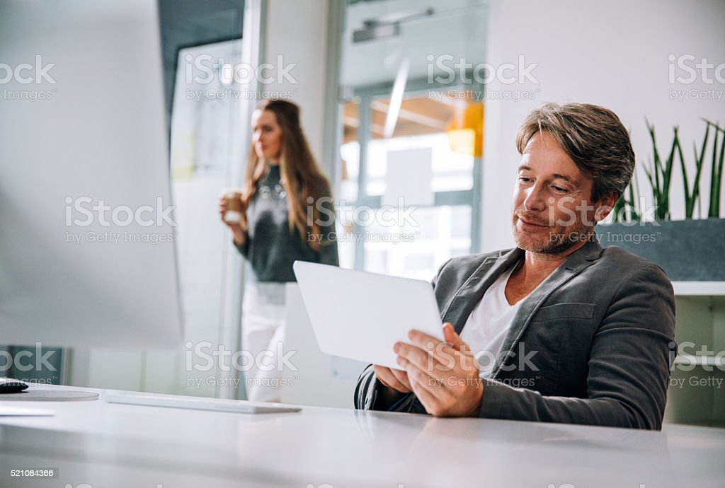 Business executive typing busines statistics on his tablet stock photo
