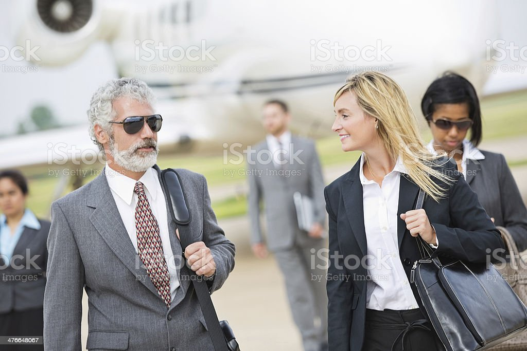 Business executives deboarding private company jet royalty-free stock photo