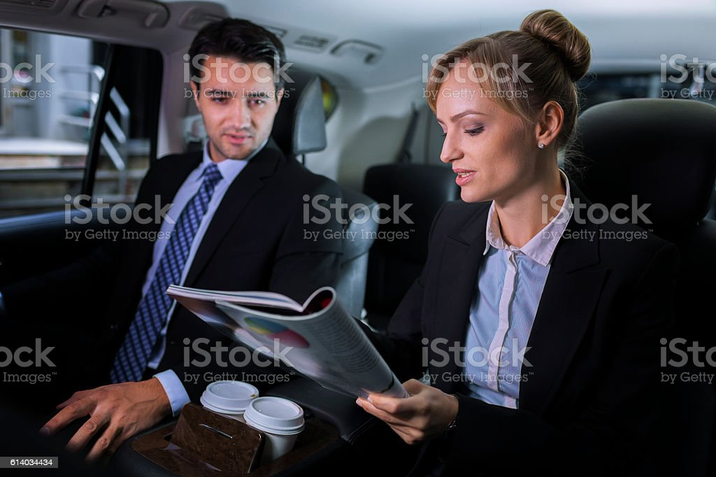 Business executives discussing progress in luxury vehicle stock photo