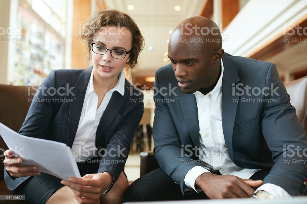 Business executives going through papers in lobby stock photo
