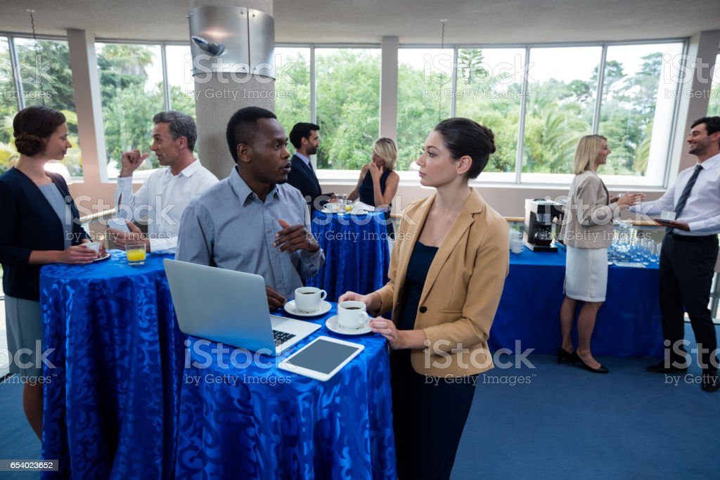 Business executives interacting with each other during break stock photo