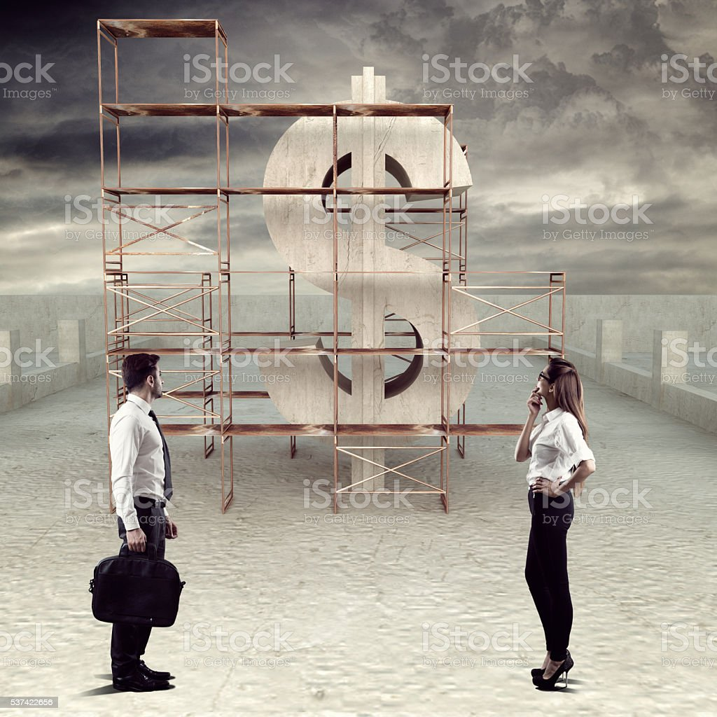 Business executives looking at under construction dollar sign stock photo