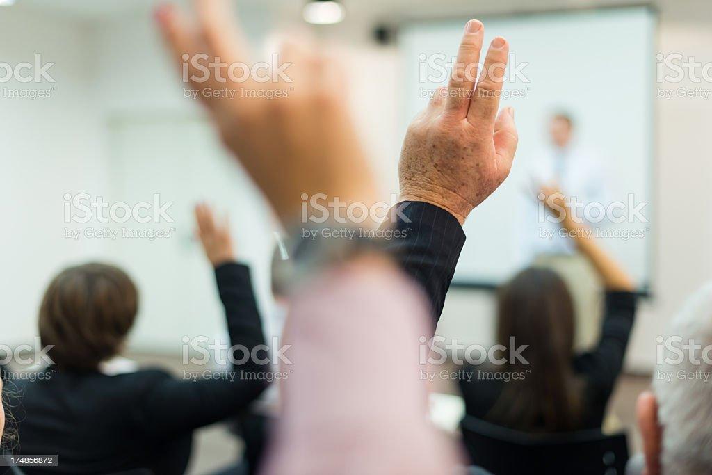 Business executives raising hands in seminar royalty-free stock photo