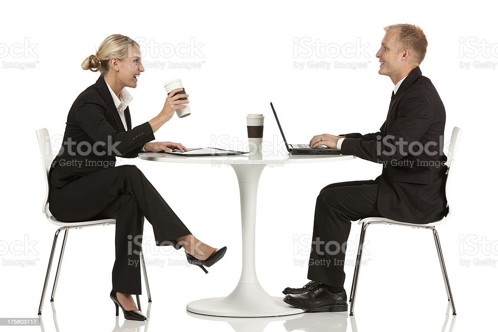 Business executives sitting across from one another at a table royalty-free stock photo