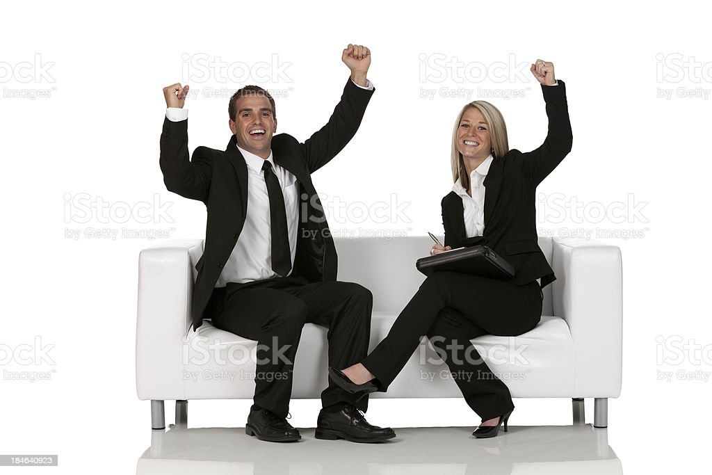 Business executives sitting on a couch and cheering royalty-free stock photo