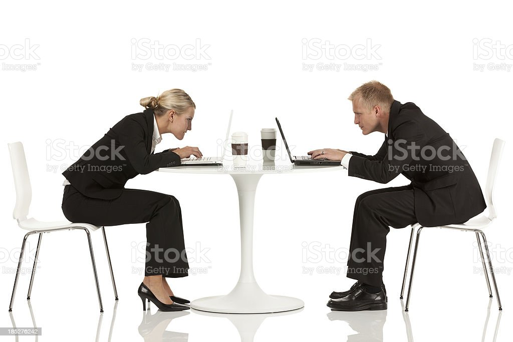 Business executives working on laptops at a coffee table royalty-free stock photo