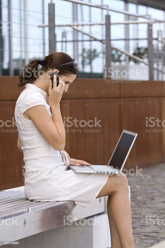 Business female outside with laptop talking on phone royalty-free stock photo