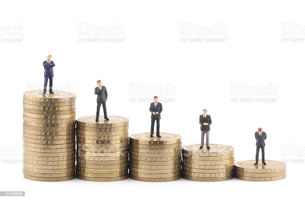 Business figures on stacks of coins stock photo