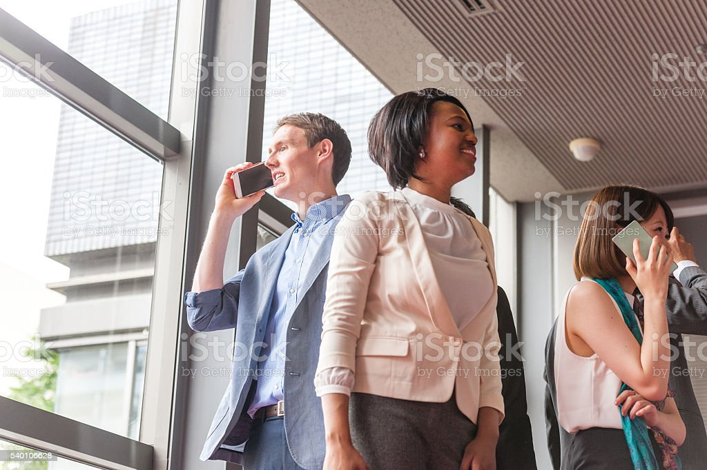 Business folk group talks mobile phone in the business...