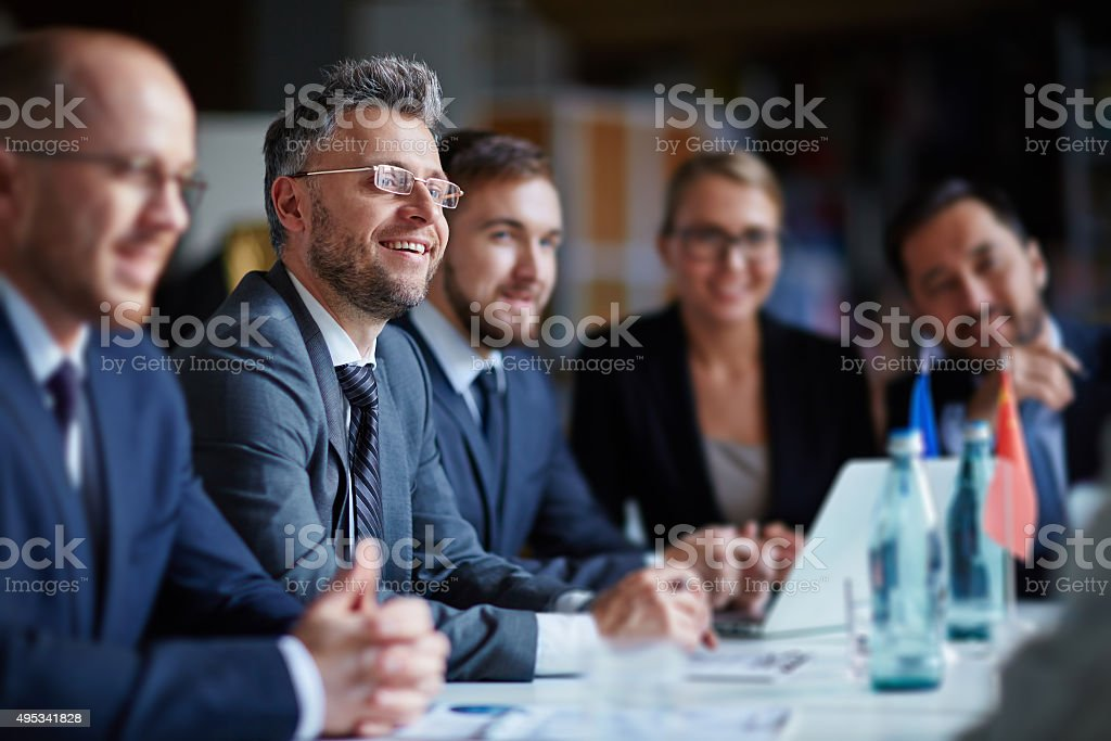 Successful businesspeople sitting at conference or seminar during...