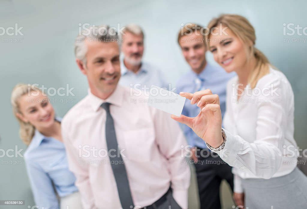 Business group holding a contact card stock photo