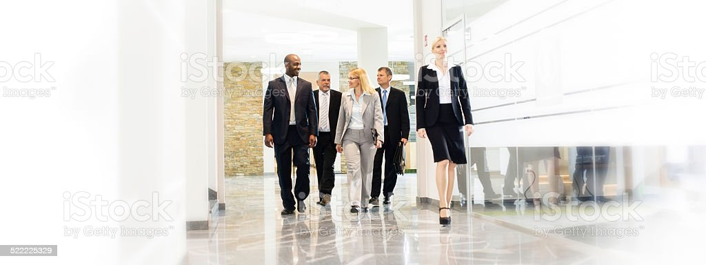 Business Group Walking in Office Corridor stock photo