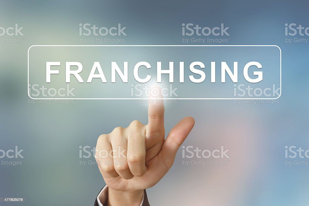 business hand clicking franchising button on blurred background stock photo