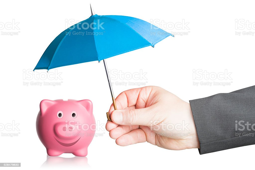 Business hand holding a protective umbrella above a piggy bank stock photo